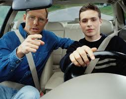 a father in a vehicle teaching his son about driver safety