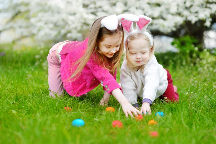 Two adorable little sisters hunting for easter egg in blooming spring garden on Easter day