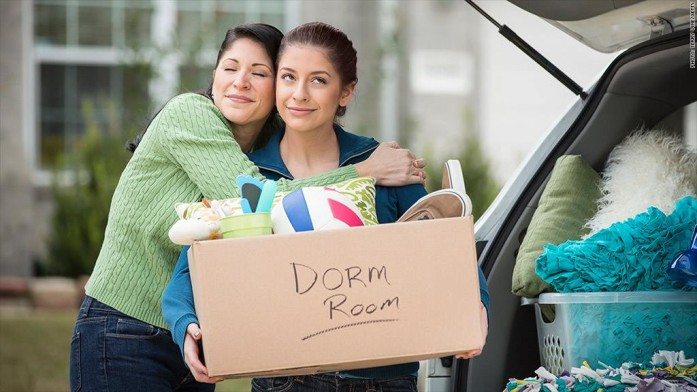 Parent hugging child leaving for college with box of possessions